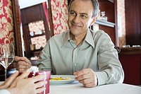 Mature man giving gift to woman in restaurant