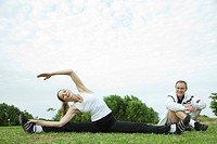 Mature couple stretching in park