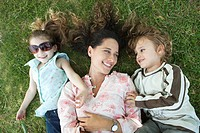 Mother lying on grass with young children