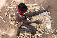 Karo boy grinding sorghum cereal to make flour. Omo Valley, Ethiopia