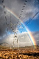 Power pylons, rainbow forms as evening sun lights up rain clouds, Mackenzie country, Canterbury, New Zealand