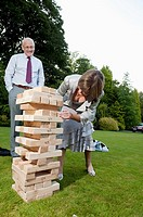 A couple playing a garden game of Jenga with a tower of wooden blocks
