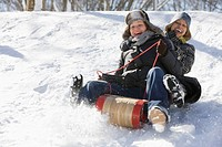 Friends sliding downhill on sled