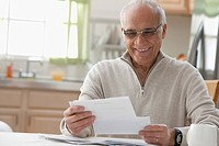 Hispanic man reading mail in kitchen