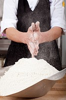 Male chef rubbing flour on hands in commercial kitchen