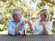 Couple toasting with wine outdoors (thumbnail)