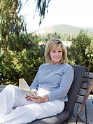 Mature woman on sun lounger with book