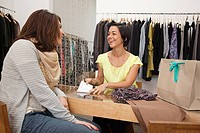 Customer and sales assistant in clothes boutique