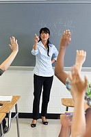 High school students with arms raised in classroom