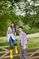 Young couple by gate in countryside