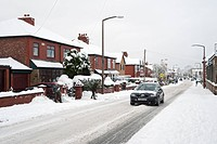 City road with car in snow, Denton, Manchester, England, winter