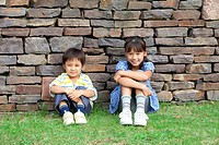 Portrait of girl and boy sitting by brick wall