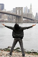 young man looking at city skyline with arms outstretched