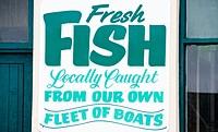 England, Cornwall, Newlyn. Fresh Fish sign outside a local fish shop.