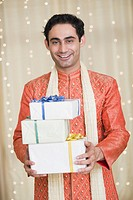 Man holding Diwali presents and smiling