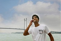 Man talking on a mobile phone with a bridge in the background, Vidyasagar Setu, Hooghly River, Kolkata, West Bengal, India