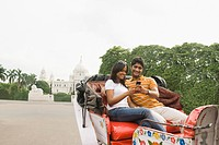 Couple sitting on a cart and using a mobile phone with a memorial in the background, Victoria Memorial, Kolkata, West Bengal, India