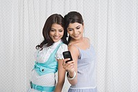 Two women text messaging on a mobile phone