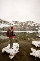 Hiker enjoying the view of Sawtooth montains with the reflection in Phyllis lake, Idaho