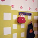 Close_up of bags on blue pegboard on yellow+white wall below stylised floral wallpaper&13,&10,&13,&10,