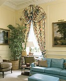 Floral curtains and draped pelmet on tall window in traditional livingroom with blue sofa and houseplant in the corner of the room