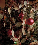 Close_up of Christamas tree decorations of bay leaves and red glass baubles