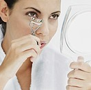 Close_up of a young woman using a eyelash curler