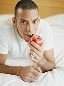 Portrait of a mid adult man lying on the bed and holding an apple
