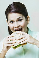 Close_up of a young woman eating a sandwich