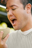 Close_up of a mid adult man eating a cantaloupe