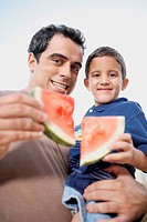 Portrait of a mid adult man carrying his son and holding slices of watermelon