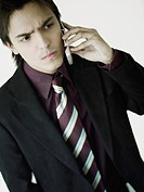 Businessman looking serious and using a mobile phone