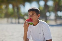 Teenage boy eating a slice of watermelon