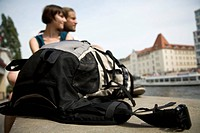 A backpack and a young couple by the Spree river, Berlin, Germany, focus on backpack
