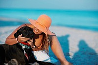 Close_up of a young woman stroking a dog on the beach