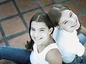High angle view of a teenage girl and her sister sitting back to back