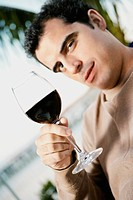 Portrait of a mid adult man holding a glass of red wine
