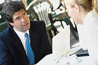 Close_up of a businessman sitting with a businesswoman