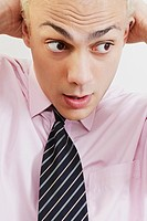 Close_up of a businessman looking surprised with his hands behind his head