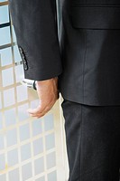 Mid section view of a businessman standing in front of a door