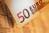 Close_up of a fifty Euro banknote on a financial newspaper