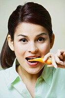 Close_up of a young woman eating a carrot