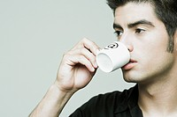 Close_up of a young man holding a cup of tea