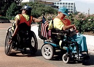 Two men with disabilities, both using wheelchairs for mobility, heading their separate ways after a long day at a national disability advocacy event.