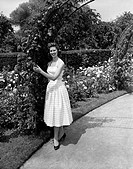 Young woman standing in rose garden