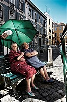 two women sitting in the shade in the Alfama district. Lisbon, Portugal