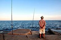A fisherman at the breakwater, Barceloneta, Barcelona, Spain