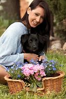 ragazza con un cesto di fiori mentre abbraccia un cane