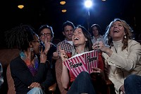 Women laughing loudly in movie theatre