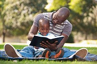 Father reading with son 4_5 on lawn, Johannesburg, Gauteng Province, South Africa